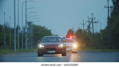 View of self-willed young man driving on modern sports car from the police. Police officer cop chasing a thief driving a patrol car on the highway at daytime. Police in pursuit.