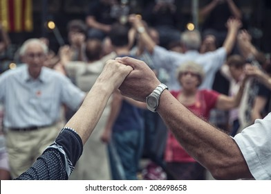 View of senior people holding hands and dancing national dance Sardana at Plaza Nova, Barcelona, Spain. It is a type of circle dance typical of Catalonia.