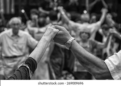 View of senior people holding hands and dancing national dance Sardana at Plaza Nova, Barcelona, Spain. It is a type of circle dance typical of Catalonia