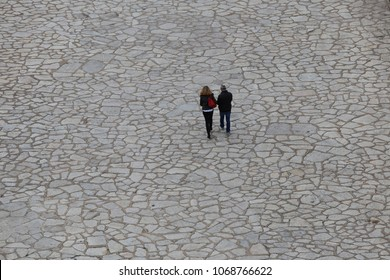 View from sete city lighthouse, France, of two people walking on the large paved quay. March, 29, 2018. Textured surface made of flat white stones. Two silhouettes in the mosaic space. Solitude symbol