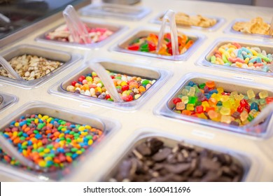 A view of several containers full of toppings in a frozen yogurt or ice cream shop setting.
