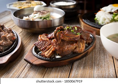 A view of several Korean entrees prepared on a wooden table surface, featuring galbi.