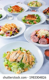 A view of several salad plates, featuring chicken Caesar and  antipasto.