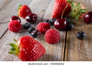 A view of several varieties of fruit and berries scattered on a wooden table surface, featuring strawberry, blueberry, raspberry and cherry.