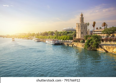 View of seville city skyline and torre del oro during sunset