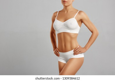View of sexy and attractive young woman standing and posing wearing white underwear. Gorgeous, slender model holding hands on her round hips.