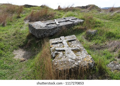 View of shabby and mossy medieval tombstones lying in overgrown grass of rocky hill, Calamita fortress