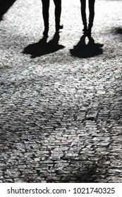 View of shadows of human persons reflected on a paved street. Long silhouettes of the people visible on the pavement, with the feet and legs. Dark long shapes on the ground. Urban abstract picture.