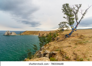 View of Shaman Rock and ritual tree with colorful ribbons Hadak in the overcast. Lake Baikal. Olkhon Island. Russia