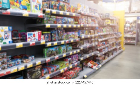 View of shelves with blurry children products in the grocery supermarket illuminated by bright light