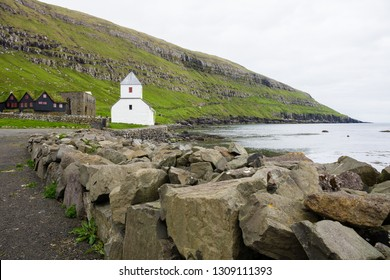View of shore with church and rocks on Faroe islands, Denmark
