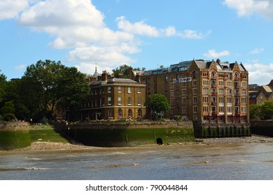 View to the shore development of the Thames at low water with the Oliver's Wharf in the Tudor gothic style - London, Great Britain - 08/04/2015