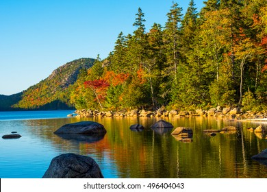 View from the shore of Jordan Pond in Acadia National Park, Maine, in Autumn during peak foliage season