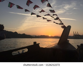 View of the shore of Muscat city in Oman seen from a traditional Dhow at sunset