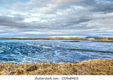 View from the shore at the town of Borgarnes, Iceland, towards the adjacent mudflats, the ocean and the land beyond, under a dramtic cloudy sky