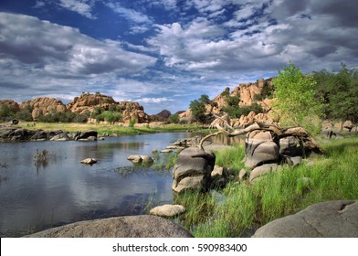 A view from the shore of Watson Lake with blue cloud filled sky and green trees with rock cliffs in Prescott, Arizona.