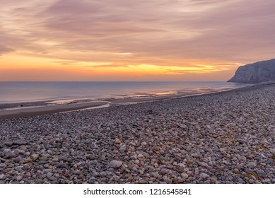 A view of Llandudno's shoreline at dawn with a red sky over the sea.  The Little Orme is in the distance.