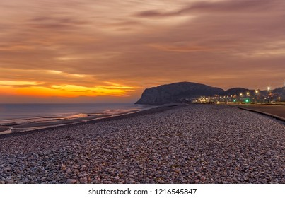 A view of Llandudno's shoreline at dawn with a red sky and lights along the foreshore.  The Little Orme is in the distance.