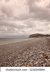 . A view of Llandudno's shoreline in the early morning with a cloud-filled sky over the sea.  The Little Orme is in the distance.