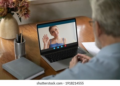 View from shoulder mature man making video call to relatives, using computer, watching webinar, learning language in internet, smiling young woman on laptop screen waving hand, chatting online