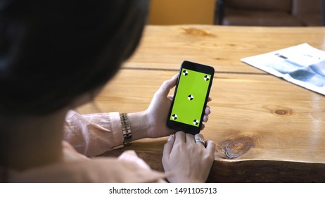 View from the shoulder of woman with brown hair in pink shirt holding iPhone in hand and looking at the chroma key green screen. Stock footage. Cellphone with chroma key screen