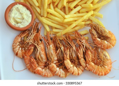 View of a shrimps and french fries on a plate.