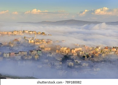 view of the shrouded in the morning fog biblical village Cana of Galilee ( Kafr Kanna ), neighborhood Nazareth in Israel
