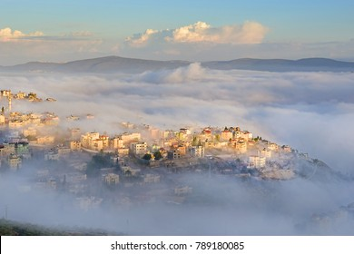 view of the shrouded in the morning fog biblical village Cana of Galilee ( Kafr Kanna ), neighborhood Nazareth in Israel,