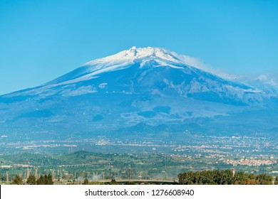 View of the sicilian landscape with smoking Etna volcano. Sicily, Italy
