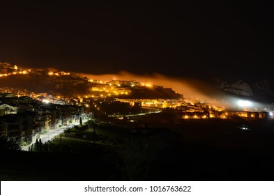 View of the Sicilian town of Troina on the Nebrodi mountains at night covered by a veil of fog with a glowing orange light. Province of Messina, Sicily.