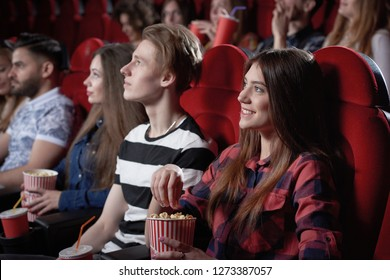 View from side of beautiful dark haired girl in red shirt enjoying watching interesting film at cinema. Pretty female viewer sitting near blond boy and eating popcorn from red cup.