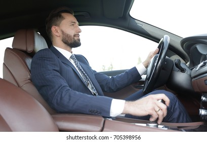 View from the side confident businessman sits at the wheel of a