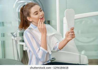 View from side of happy female patient looking at mirror and enjoying beautiful smile in dental office. Young woman visiting dentist and treating teeth. Concept of dentistry and stomatology.