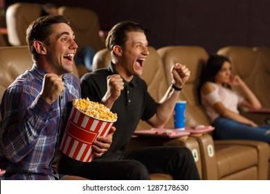 View from side of happy males cheering up and laughing at funny comedy in cinema hall. Two friends eating popcorn and shouting during movie watching. Concept of happiness and funny pastime.