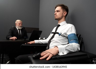 View from side of honest man sitting with indicators on fingers and telling truth. Serious man answering while elder man in black smart suit asking and checking diagrams. Concept of lie detector.