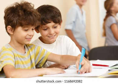 View from side of interested little pupils sitting together at table and writing in copybook. Smart classmates in process of learning new material in classroom. Concept of studying.