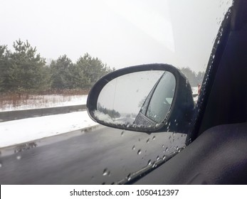 view of the side mirror while driving from the driver's perspective. Snow on the mirror, drops of water on the glass. In the background a winter landscape and snow.