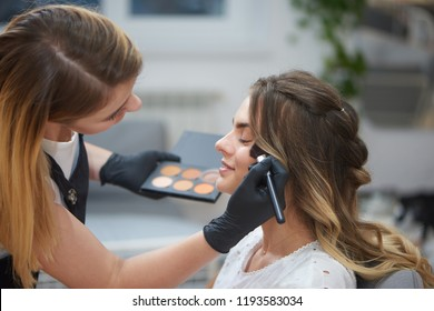 View from side of qualified makeup artist doing visage to young woman in beauty salon. Beautician in uniform and gloves contouring face of client sitting in chair and enjoying process.