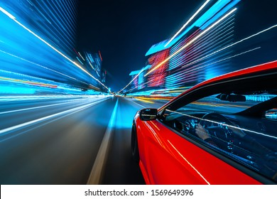View from Side of a Red Muscle Car moving in a night city, Blured road with lights with car on high speed. Concept rapid rhythm of a modern city. - Shutterstock ID 1569649396