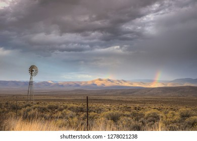 A view from the side of the road on a rainy day in the Karoo, South Africa. A windmill in the foreground and a rainbow in the background.