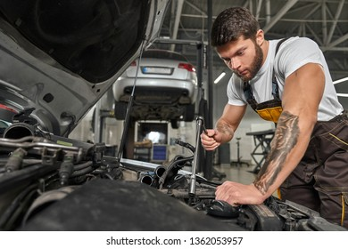 View from side of strong man wearing coverall repairing engine in automobile. Muscular mechanic working in workshop and fixing damage in car. Concept of auto service and maintenance.