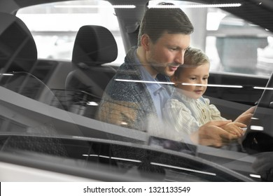 View from side window, father and son sitting inside of automobile. Parent and child sitting in car cabin, in driver's seat looking at steering wheel. Potential buyer testing vehicle.