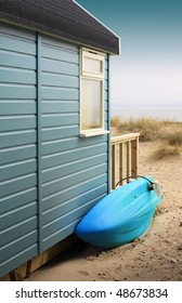 View of the side of a wooden beach hut with a blue surf board, looking towards the beach. Located in Christchurch, Hampshire UK.