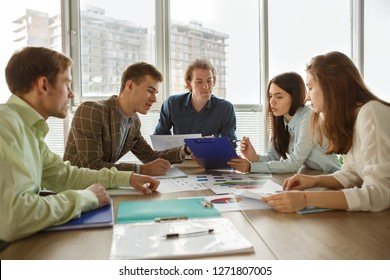 View from side of young colleagues talking and sharing opinions during conference in office. Pretty women and smart men sitting at table and looking at tables and statistics. Concept of business.