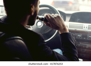 View from the side of a young man smoking an e-cigarette as he drives his car on an urban street.