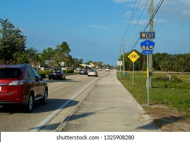 View from sidewalk of Bonita Beach Road during winter tourist season with traffic and road signs.