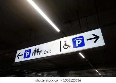View of a signage showing the way to Family Parking, Disabled Parking and Exit inside a public parking lot