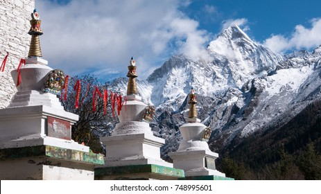 View of Siguniang Mountain from Lama Temple, Siguniangshan NP, Sichuan, China. Placards/flags read 'Om Mani Padre Hum' in Tibetan, a famous Sanskrit mantra embodying the teachings of Buddha.