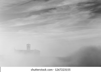 A view of a silhouette of St.Francis church in Assisi in the middle of mist beneath a deep sky with clouds