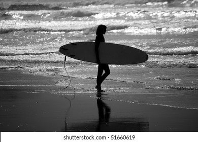 View of a silhouette of a surfer girl holding the board walking toward the sea.